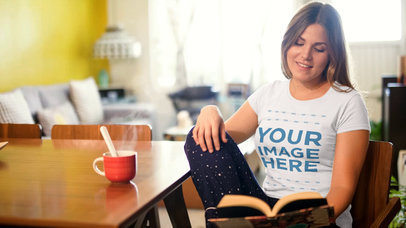 Cinemagraph Video Mockup of a Pretty Girl Having a Coffee While Wearing a T-Shirt and Reading a Book a13478
