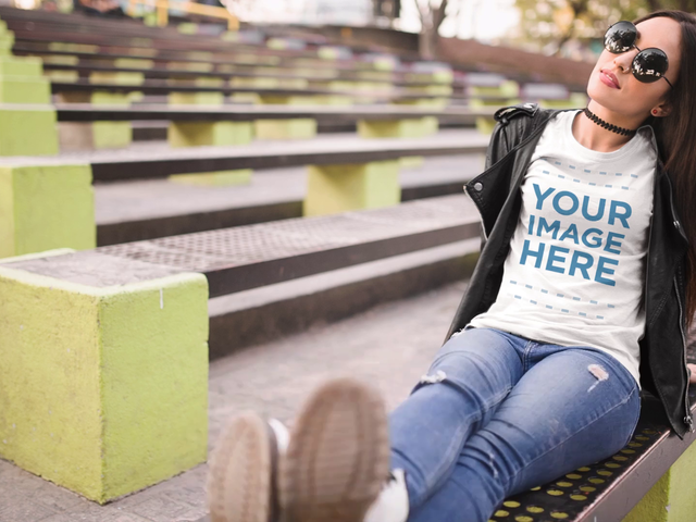 Mockup Video of a Trendy Girl Lying Down and Moving Her Foot at an Urban Environment While Wearing a T-Shirt and Sunglasses a13513