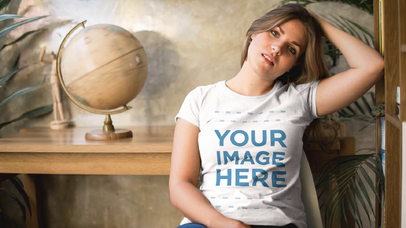 Pretty Girl Sitting on a Chair Wearing a T-Shirt While World Globe Map Spinning Mockup Cinemagraph a13481