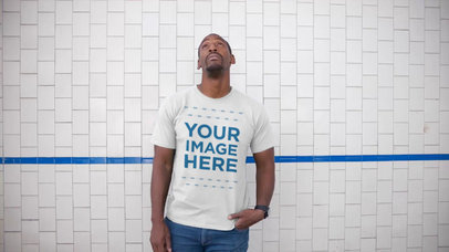 Mockup Video of a Black Man Wearing a Round Neck T-Shirt Against a White Wall Tile a13122