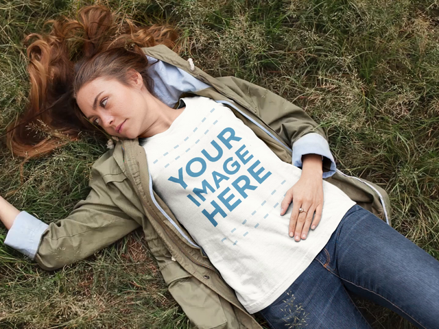 Pretty White Girl Lying on the Grass While Wearing a Round Neck Tee Playing With Her Hair Cinemagraph Mockup a13311