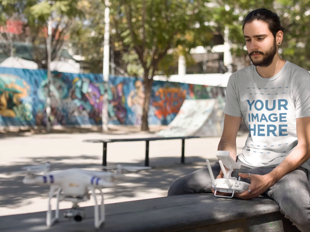 Hipster Young Man Wearing a Round Neck Tee While Playing With Remote Control Helicopter Cinemagraph Mockup a13368
