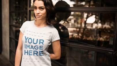 Pretty Girl Wearing a Round Neck Tee Against a Glass Mockup Cinemagraph a13441