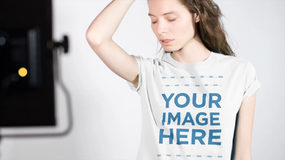 Smiling Young Woman Wearing a T-Shirt at a Photo Session Mockup Video a13404b