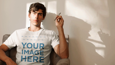 Young White Man Playing With Pen In a Room Wearing a Round Neck T-Shirt Mockup Cinemagraph a13331