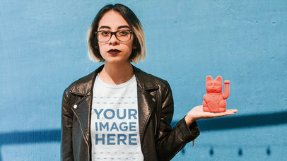 Cinemagraph Mockup Featuring a Young Girl Wearing a Round Neck Tee and Leather Jacket While Holding a Pink Manekineko a13606