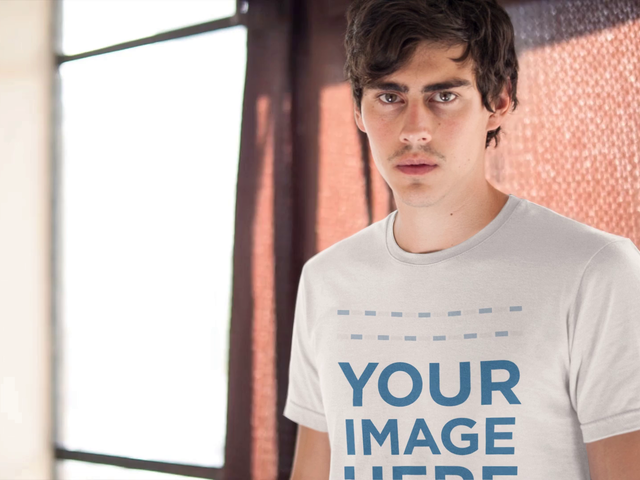Mockup Cinemagraph of a Young Guy Wearing a Short Sleeved Tee With a Curtain Moving in the Back a13329