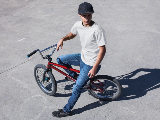 Mockup Stop Motion of a Young Man Wearing a Round Neck Tshirt While Sitting In His Bike a13354