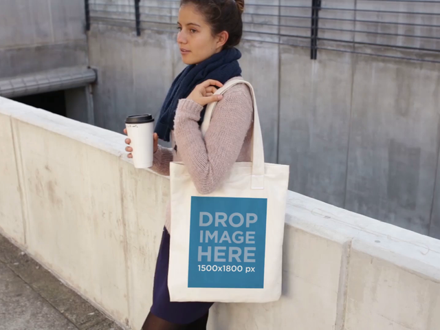 Young Girl Holding a Tote Bag While Waiting And Drinking A Coffee Video Mockup a13770