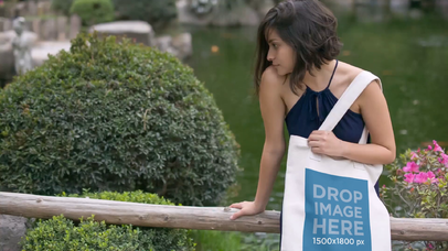 Mockup Video Of A Pretty Girl Holding A Tote Bag While Near A Pond a13877