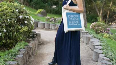 Pretty Girl Holding A Tote Bag Smiling In A Garden Path Video Mockup a13879