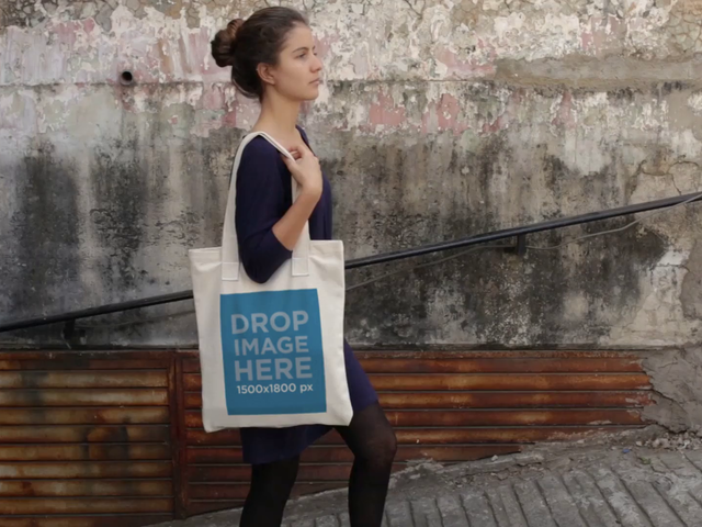 Beautiful Girl Carrying A Tote Bag While Walking In A Leaning Street Mockup Video a13771