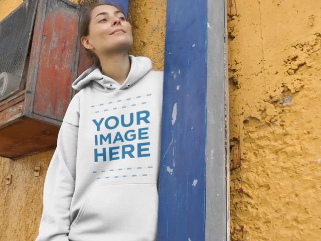 Pullover Hoodie Mockup Video Of A Young Girl Lying On A Blue Metal Structure And Yellow Wall a13099