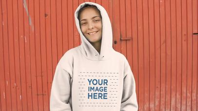 Trendy Woman Wearing a Hoodie Over Her Head With A Red Metal Door In The Background Video Mockup a13097