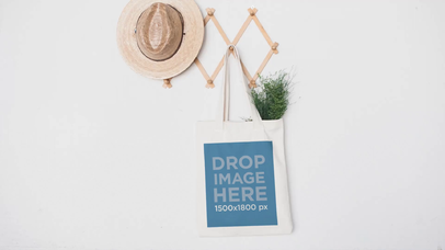 Tote Bag Swinging On A Wall Hanger On A White Wall Video Mockup a13763