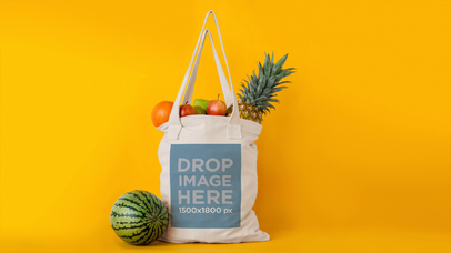 Tote Bag Stop Motion With Fruits Dissapearing From It Mockup Against Yellow Background a13711