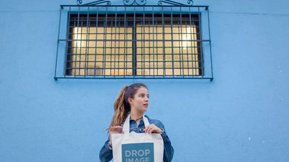 Beautiful Girl Holding A Tote Bag While Standing With A Blue Bricks Wall Behind Mockup Video a13716
