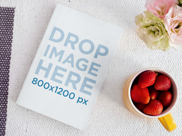Mockup Of A Book Lying On A Friendly Desk While Strawberries Dissapear From A Cup Stop Motion a13872