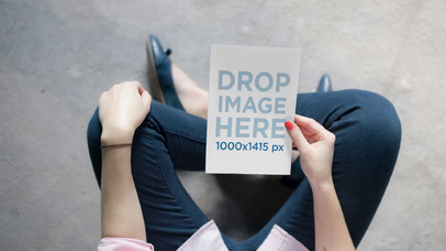 Video Mockup Of A Teenager Girl Holding A Flyer On Her Hand While Sitting In A Concrete Floor a13922