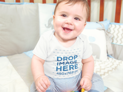 Mockup Of A Smiling White Baby Sitting On His Crib While Wearing A Onesie a13959