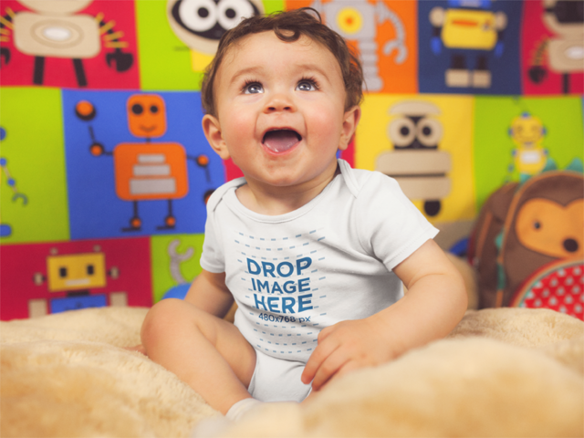 Happy Baby Smiling While Sitting Down Wearing A Onesie Mockup a14027