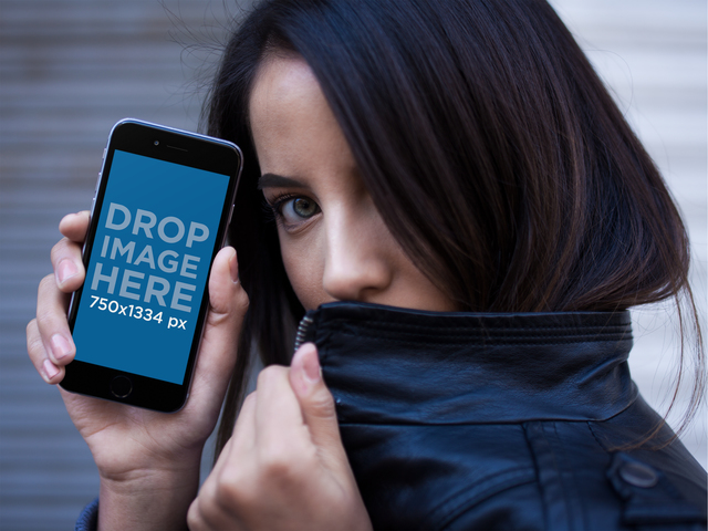 Mockup Of A Girl With Green Eyes Hiding With Her Leather Jacker While Showing A Black iPhone 6 a14036