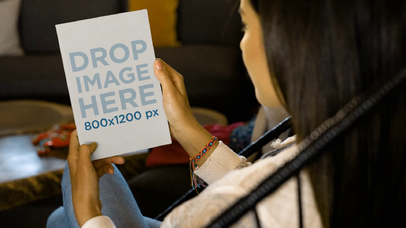 Video Of A Girl Holding A Flyer On Her Hands While Sitting On An Acapulco Chair Mockup a14009