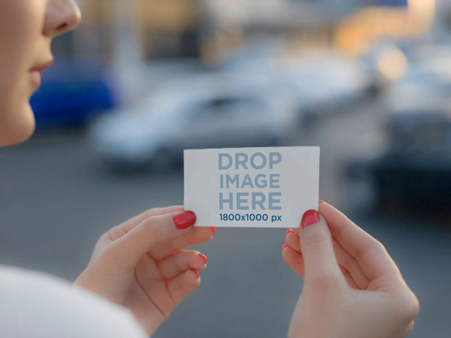 Pretty Girl Holding A Business Card In The City While Cars Passing By Mockup Video a13919