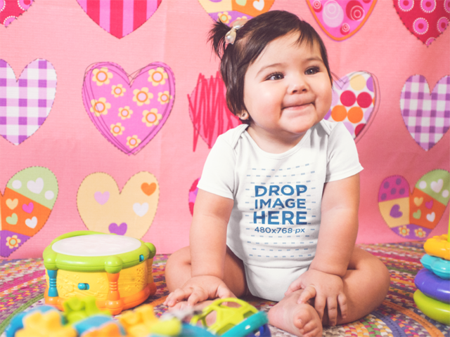 Mockup Of A Very Happy Baby Girl Sitting Down On Her Playing Room While Wearing A Onesie a14052