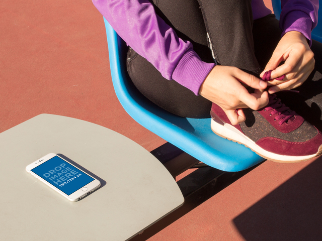 Mockup Of A White iPhone 6 Lying Over A Table While A Girl Is Tying Her Laces In A Plastic Chair a14094