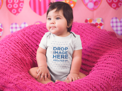 Beautiful Little Baby Girl Sitting On A Pink Sofa While Wearing A Onesie a14047