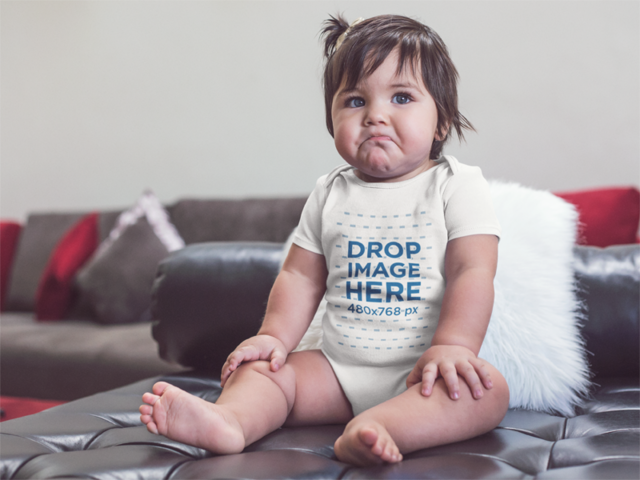 Little Baby Making Funny Faces While Wearing A Onesie And Sitting In A Black Leather Sofa Mockup a14049