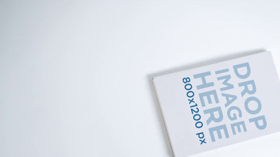 Mockup Video Hovering over a Book Lying over a White Surface a13981