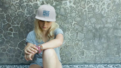 Blonde Skater Girl Wearing a Snapback While Sitting Down Against a Wall Video Mockup a14141
