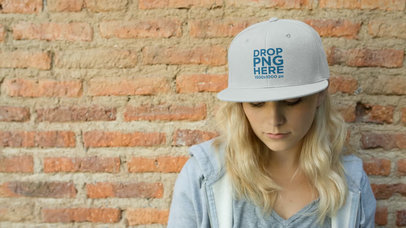 Video Mockup of a Young Woman Wearing a Snapback Hat While Sitting Down Against a Bricks Wall a14139