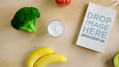 Book Lying on a Wooden Table with Water Vegetables and Fruits Surrounding It Mockup Video a14177