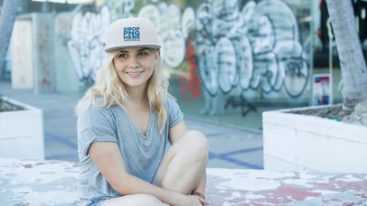 Young Blonde Girl Wearing a Snapback Hat While Sitting at a Skate Park Mockup Video a14137
