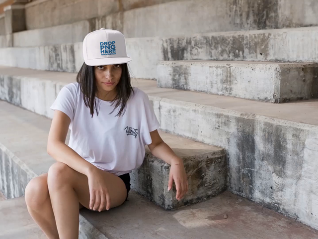 Young Girl Wearing a Snapback Hat While Making Faces Sitting in Some Concrete Stairways Mockup Video a14203