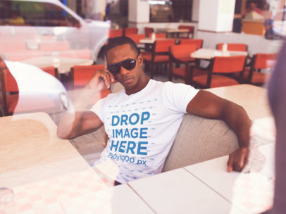 Mockup of a Man Sitting down in a Diner Restaurant While Wearing a T-Shirt and Sunglasses a14219