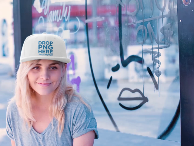 Young White Skater Girl Wearing Snapback Hat While Sitting in a Bus Stop with Graffities Mockup Video a14138