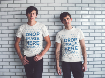 Two Young Friends Hanging Out Wearing Same Round Neck Tees While Lying Against a White Bricks Wall Mockup a13411