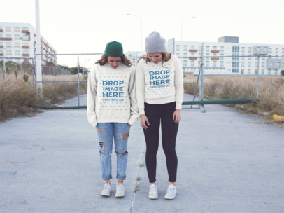 Two Girls Wearing Same Crewneck Sweatshirts While Looking at Their Shoes in an Industrial Area a13342