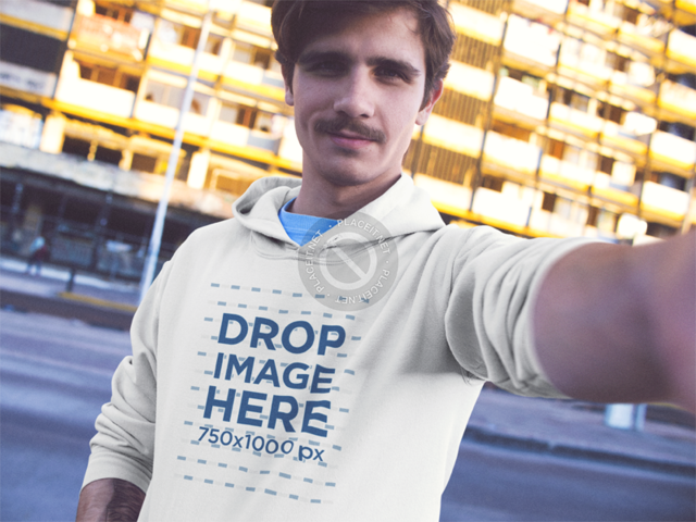 Selfie Mockup of a Young White Man Wearing a Pullover Hoodie in the City a13611