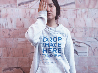 Asian Girl Putting Her Hand in an Eye While Wearing a Heather Pullover Hoodie Near a Pink Wall a12693
