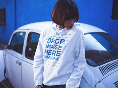 Young Hipster Girl Wearing a Hoodie While Leaning Over a Beetle And Looking Down Mockup a12678