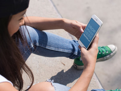 Mockup of a Young Girl Using Her iPhone 6 While Sitting Down at the Skate Park a14210