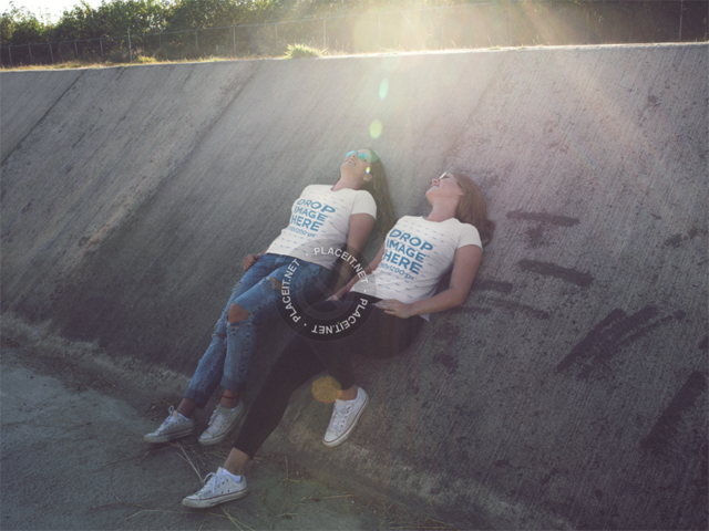 Two Girls Wearing Matching Tshirts While Relaxing in an Industrial Area Mockup a13338