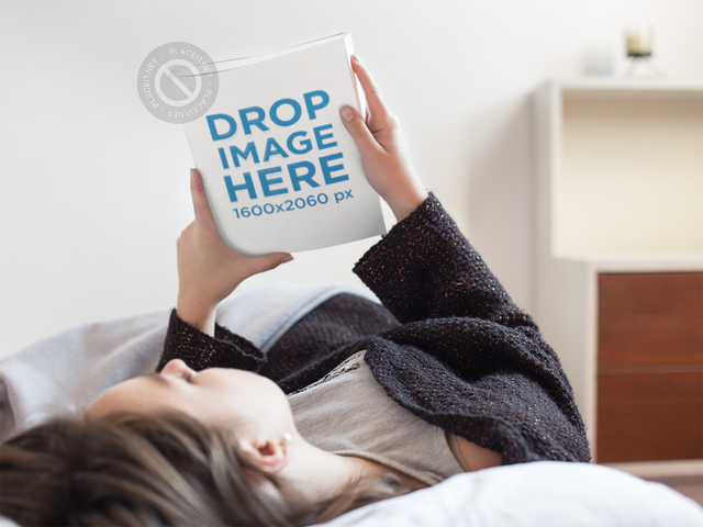 Young Girl Looking at a Book Cover While Lying down in Her Bed Mockup a14302