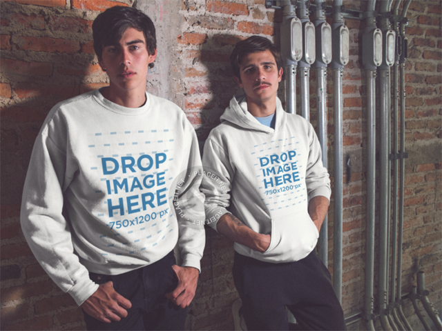 Mockup of Two Young Fellas Wearing a Crewneck Sweatshirt and a Pullover Hoodie While Lying Against a Bricks Wall a13415