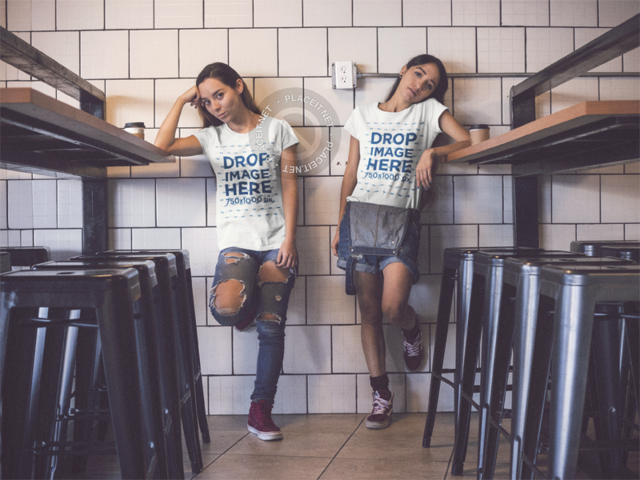 Young Girls Wearing Same T-shirts While Hanging Out in a Room With a White Bricks Wall Mockup a13347